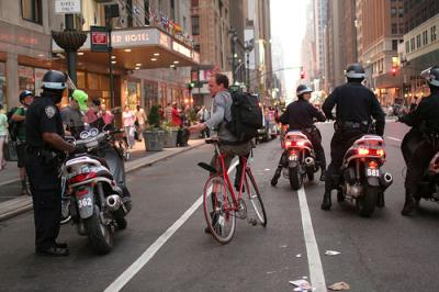 Cyclists being ticketed by 4 policeman.  Photo by Irene  Tejaratchi